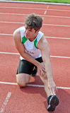 Young male sprinter stretching before a race. Young male sprinter stretching on the floor before a race in a stadium Royalty Free Stock Photo