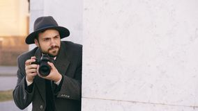 Young male spy agent wearing hat and coat photographing criminal people and hiding behind the wall Stock Images