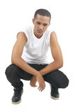 Young male staring at the ground. Young mixed race male wearing a white short sleeve shirt and black jeans on an isolated background staring at the ground Royalty Free Stock Images