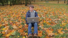 Young male it startup programmer working using laptop on the carpet of fallen leaves in autumn park dolly shot. Young male it startup programmer working outdoors stock video footage