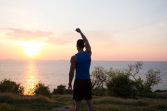 Young male stretching before fitness training session at the park. Healthy young man warming up outdoors. Sunset or sunrise in the Stock Image