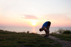 Young male stretching before fitness training session at the park. Healthy young man warming up outdoors. Sunset or sunrise in the Stock Images