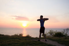 Young male stretching before fitness training session at the park. Healthy young man warming up outdoors. Sunset or sunrise in the Stock Photo