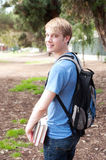 Young male student. Standing with backpack and books Stock Images
