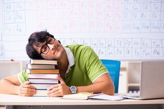 The young male student chemist in front of periodic table. Young male student chemist in front of periodic table stock photos