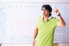 The young male student chemist in front of periodic table. Young male student chemist in front of periodic table royalty free stock photography