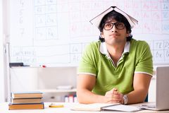 The young male student chemist in front of periodic table. Young male student chemist in front of periodic table stock images