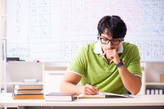The young male student chemist in front of periodic table. Young male student chemist in front of periodic table royalty free stock photo