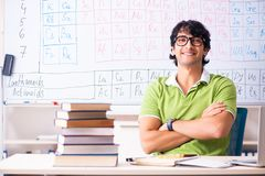 The young male student chemist in front of periodic table. Young male student chemist in front of periodic table stock photography