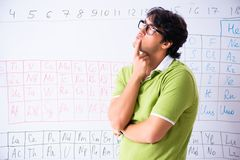 The young male student chemist in front of periodic table. Young male student chemist in front of periodic table royalty free stock photos