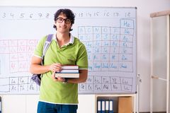 The young male student chemist in front of periodic table. Young male student chemist in front of periodic table royalty free stock image