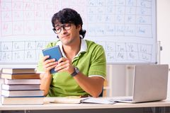 The young male student chemist in front of periodic table. Young male student chemist in front of periodic table stock photo