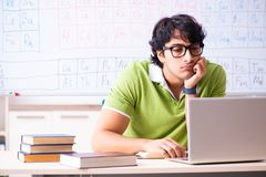 The young male student chemist in front of periodic table. Young male student chemist in front of periodic table royalty free stock images