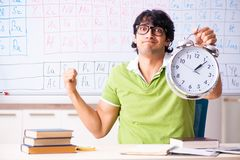 The young male student chemist in front of periodic table. Young male student chemist in front of periodic table stock image