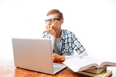 Young male student doing lessons with laptop and books sitting at table in Studio on white background. Young male student doing lessons with laptop and books Stock Images