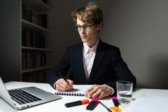 Determined and confident young businessman works late hours in office on project to meet deadline. Young male student or employee doing home task or project at Royalty Free Stock Image