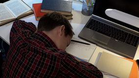 Young male student fallen asleep on table while doing homework, tiredness. Stock photo stock image