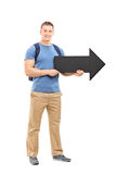Young male student holding a big black arrow. Full length portrait of a young male student holding a big black arrow pointing right isolated on white background Stock Photos
