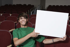Young Male Student Holding Billboard In Classroom Stock Photography