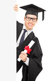 Young male student holding diploma and standing behind blank pan. Young male student holding a diploma and standing behind blank panel isolated on white Royalty Free Stock Images