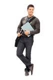 Young male student holding a notebook. Full length portrait of a young male student holding a notebook isolated on white background Royalty Free Stock Photo
