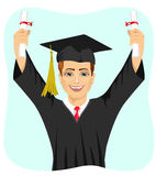 Young male student holding two diplomas with both hands on graduation day. On white background Royalty Free Stock Images