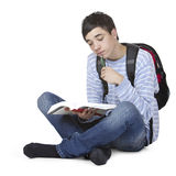 Young male student learning from book. Young male student sitting on floor and learing from study book. He has satchel on back. Isolated on white Stock Images