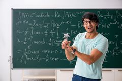 The young male student mathematician in front of chalkboard royalty free stock image