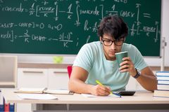 The young male student mathematician in front of chalkboard stock photos