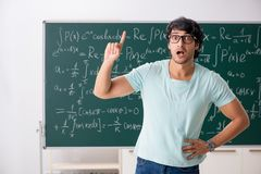 The young male student mathematician in front of chalkboard. Young male student mathematician in front of chalkboard royalty free stock images