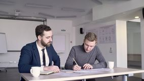 Young male student and professor of architecture are working together. People are sitting at the wooden table with papers and cups of coffee on, in bright stock video