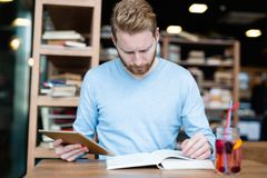 Young male student reading in coffee shop. Alone Royalty Free Stock Image