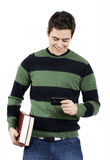 Young male student reading text message. Handsome young male student laughing carrying books and checking his text message on his cell phone Royalty Free Stock Images