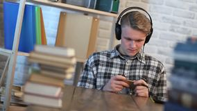 Young male student reading text message on phone. Cheerful student in library chatting on mobile phone while listening to music with headphones. Handsome stock video