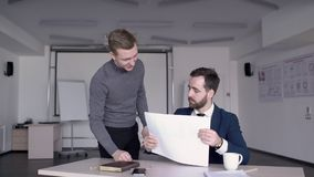 Young male student is showing his project to the professor of architecture on exam. Mature professional in suit and tie is sitting in the lecture room, at the stock footage