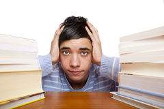 Young male student sitting frustrated on desk. Young handsome student sitting on a desk between study books and looks frustrated. Isolated on white Royalty Free Stock Photo