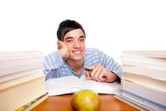 Young male student sitting between study books. Young handsome student smiles happy and sits between study books at desk. Isolated on white Royalty Free Stock Images