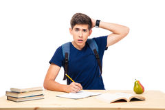 Young male student sitting at the table. And writing in notebook isolated on a white background. Looking at camera Stock Photography