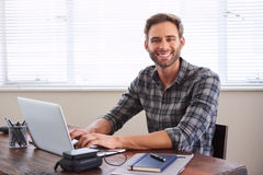 Young male student smiling at camera while working on assignment. Young caucasian male student smiling at the camera with his hands on the keyboard of his laptop Stock Photos