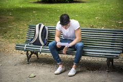 Young Male Student Studying at the Bench Seriously. Young Male Student Sitting on the Bench with Legs Crossed next to his Back Pack While Studying his Lessons Royalty Free Stock Photos