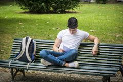 Young Male Student Studying at the Bench Seriously. Young Male Student Sitting on the Bench with Legs Crossed next to his Back Pack While Studying his Lessons Royalty Free Stock Photography