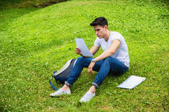 Young Male Student Studying in City Park. Young Male Student Studying his Lessons while Lying on Grass in City Park, Smiling at Camera Royalty Free Stock Images