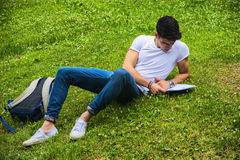 Young Male Student Studying in City Park. Young Male Student Studying his Lessons while Lying on Grass in City Park, Smiling at Camera Stock Photography