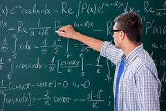 The young male student studying math at school. Young male student studying math at school stock photo