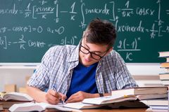 The young male student studying math at school. Young male student studying math at school royalty free stock image