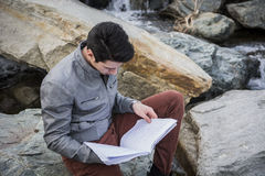 Young male student studying outdoors sitting on rocks. Alongside a stream reading his notes Royalty Free Stock Photography