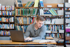 Young male student typing on laptop in the university library.  Royalty Free Stock Photo