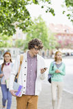 Young male student using cell phone with friends in background on street Stock Photos