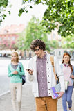 Young male student using cell phone with friends in background on street Royalty Free Stock Photos