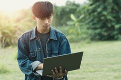 Young male student using laptop while goes camping in forest in relaxing vacation. Young male student using laptop while goes camping in forest in relaxing stock images